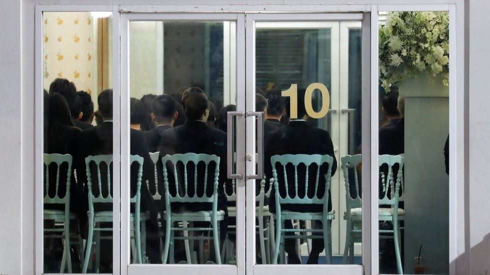 People are seen through a glass door as they attend a funeral of Vichai Srivaddhanaprabha in Bangkok