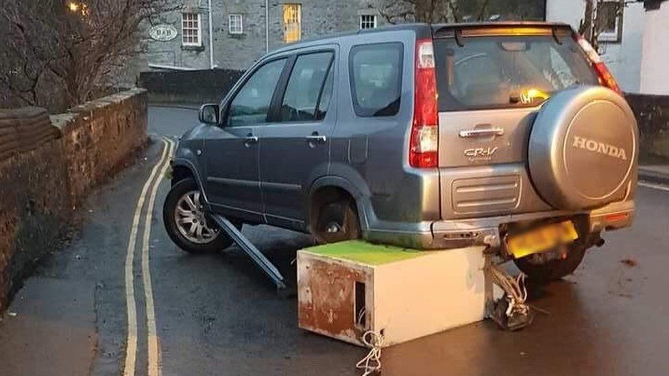 ATM wedged beneath parked car