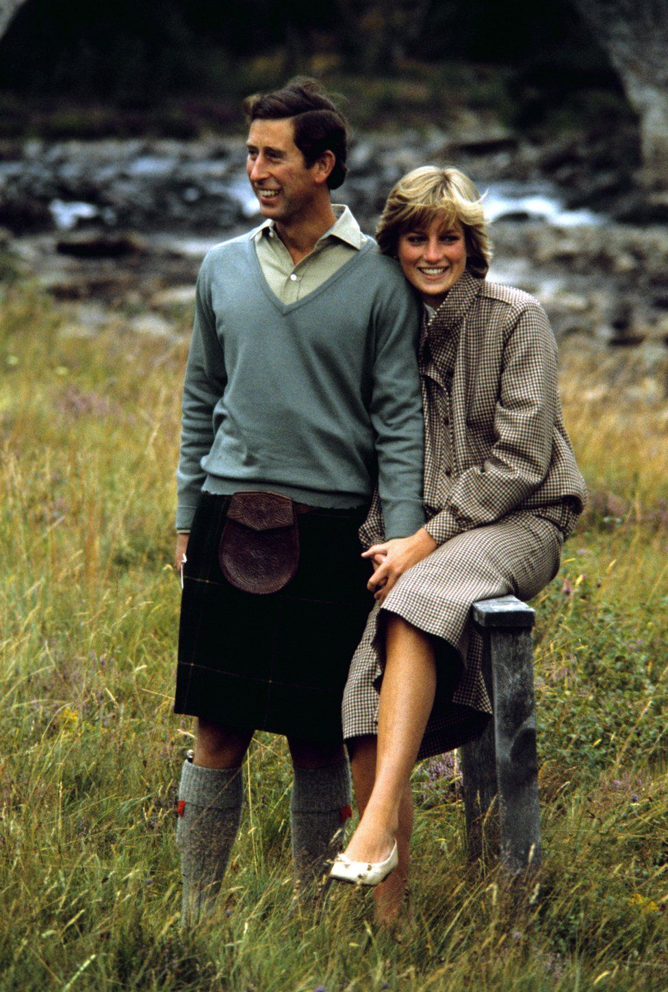 Charles and Diana sit together by the banks of a river