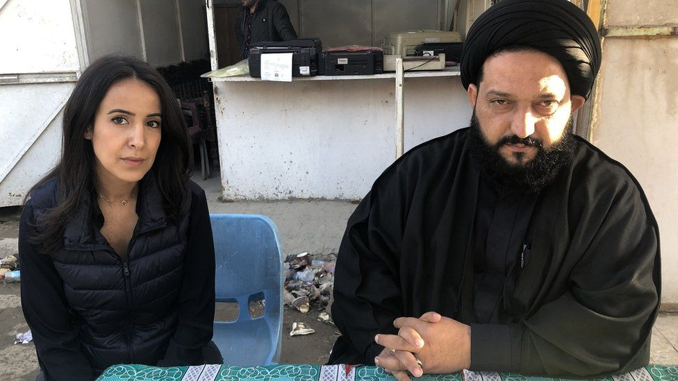 The BBC's Nawal al_Maghafi with a cleric outside Sadr City court