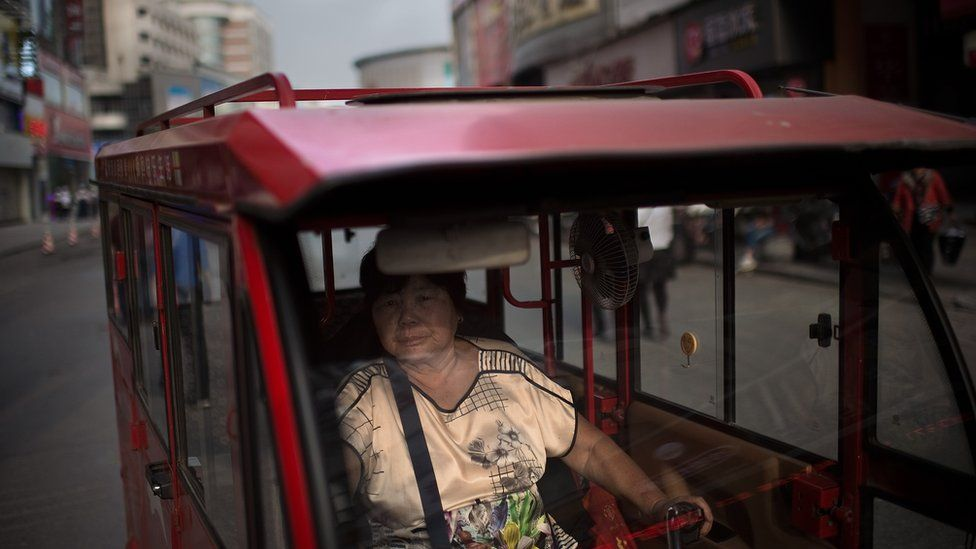 A woman drives her tuk tuk (taxi) looking for customers in a street in Zhengzhou, China