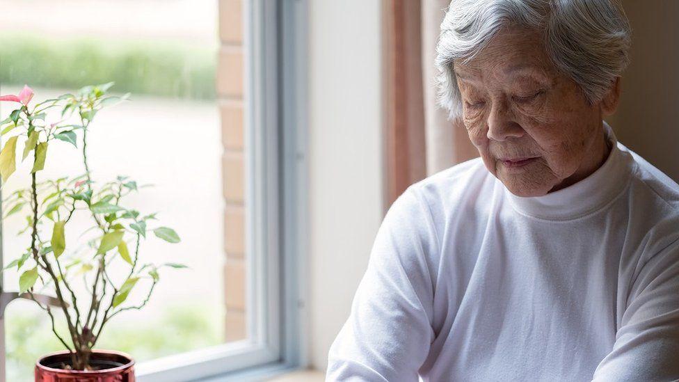 Una mujer de edad, sentada cerca de una ventana con los ojos cerrados