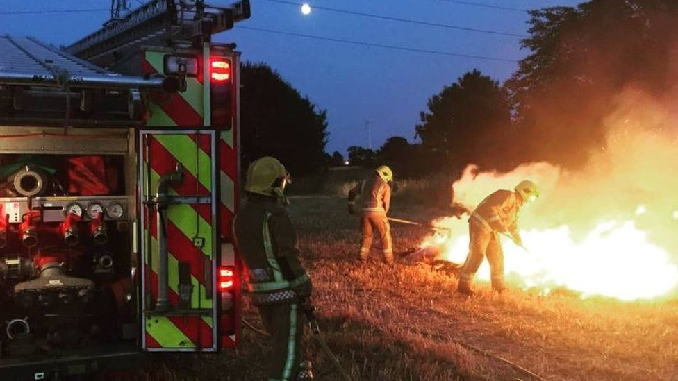 Fire fighters tackle a fire on farmland in Norfolk