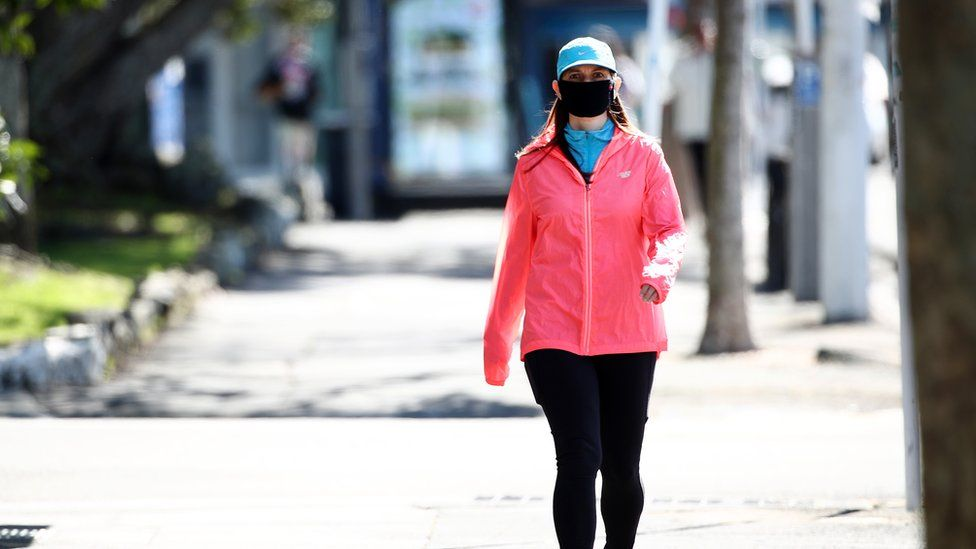 A woman walking wearing a mask in Auckland