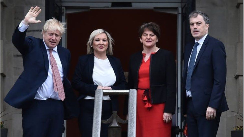 Boris Johnson waving and standing next to the first and deputy first ministers and NI Secretary Julian Smith