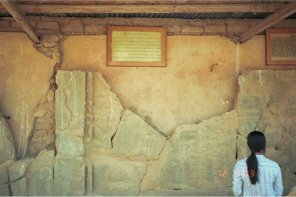 Woman looks at relief broken into fragments