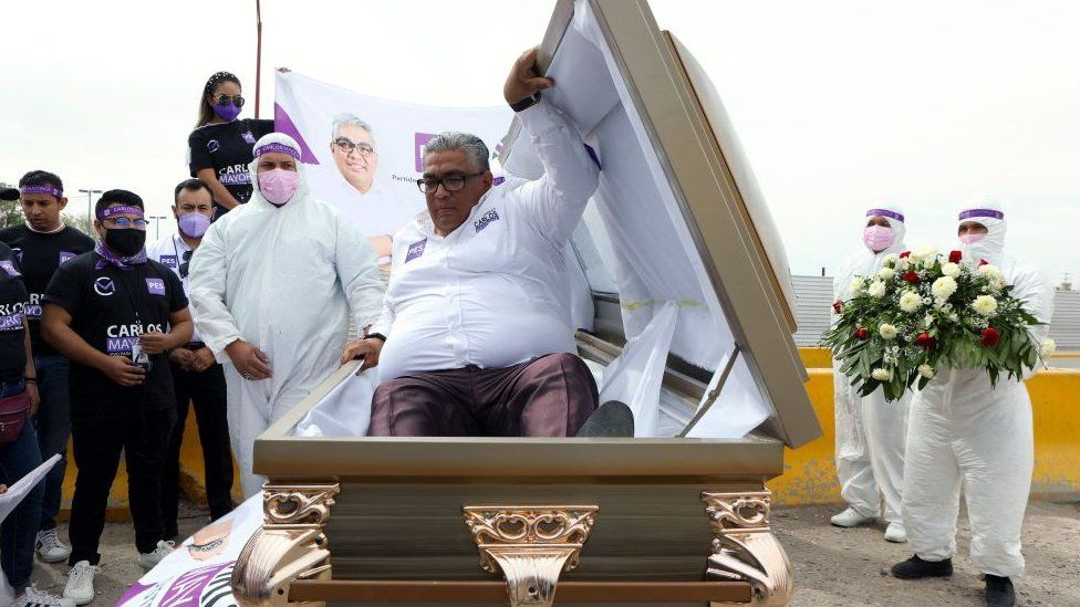 The Mexican candidate for federal deputy of the Social Encounter Party, Carlos Mayorga, launches his campaign inside a coffin, to highlight the country's many thousands of deaths from the coronavirus pandemic and cartel-related violence, at the Zaragoza-Ysleta international bridge in Ciudad de Juarez, Mexico, on 6 April 2021