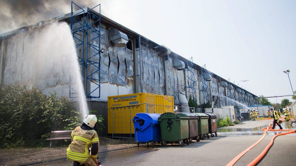 Firefighters attempt to extinguish a fire in a hall at a convention centre being used to accommodate refugees in Duesseldorf, Germany, 7 June 2016