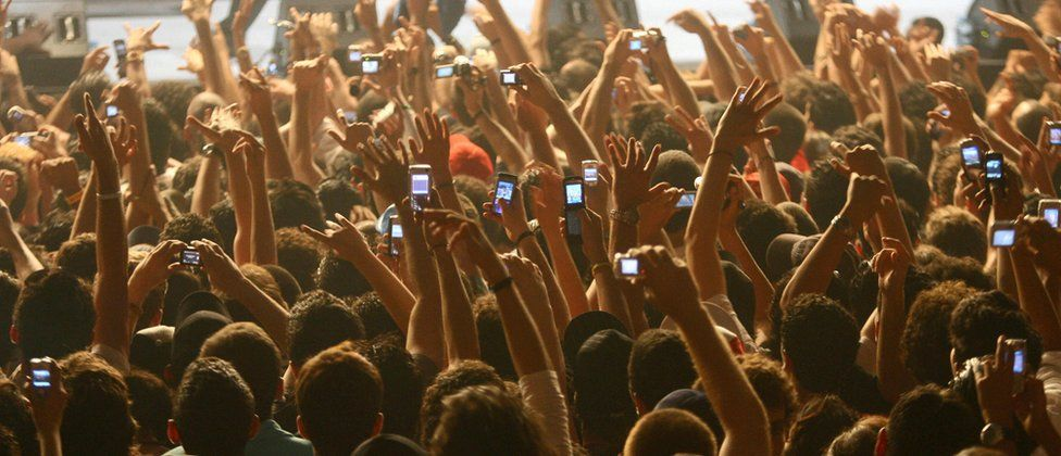 Concertgoers holding up mobile phones
