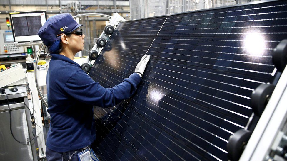 An employee makes a final inspection on panels during a tour of an REC solar panel manufacturing plant in Singapore, May 5, 2017.