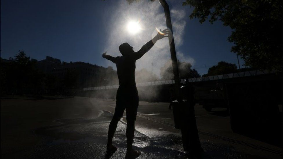 A man cools off under a water sprinkler during a hot summer day in Vienna, Austria July 30, 2020.