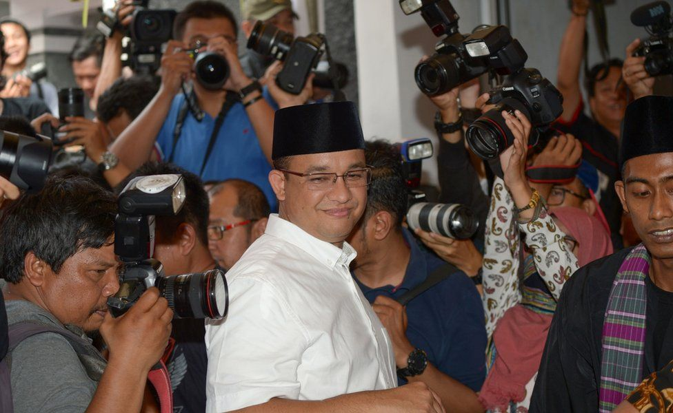 Candidate for Jakarta governor, Anis Baswedan (C) is surrounded by journalists as he arrives at a poll station in Jakarta on 19 April 2017.