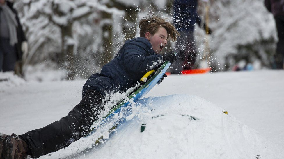 A boy tries to jump up a mound while sledding