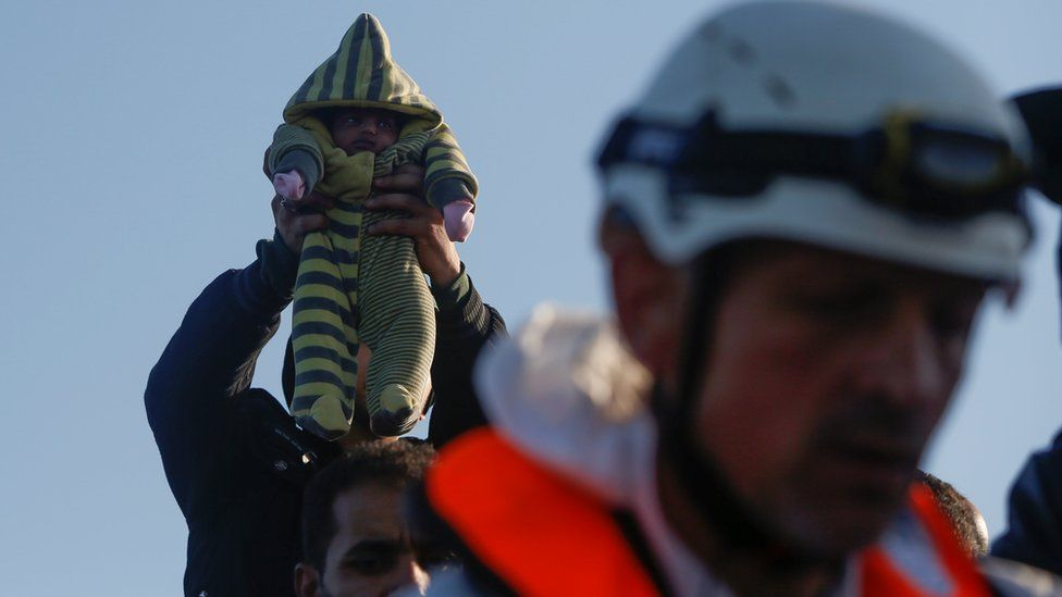 A 12-day-old Somali baby is lifted up by a migrant on a wooden boat during a rescue operation conducted by the Malta-based NGO Migrant Offshore Aid Station (MOAS) ship Phoenix in the central Mediterranean in international waters off the coast of Sabratha in Libya, April 15, 2017.