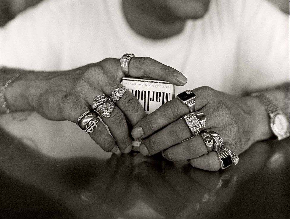 A man with lots of rings on his fingers clutches a packet of cigarettes