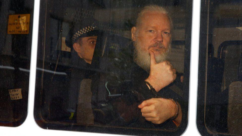 Julian Assange pictured in a police van