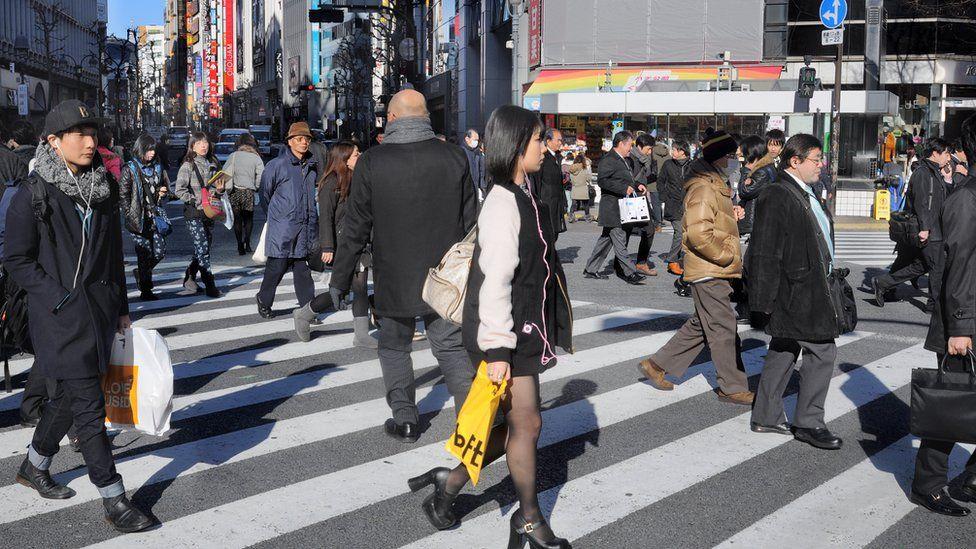 Japanese people cross a street in Shibuya