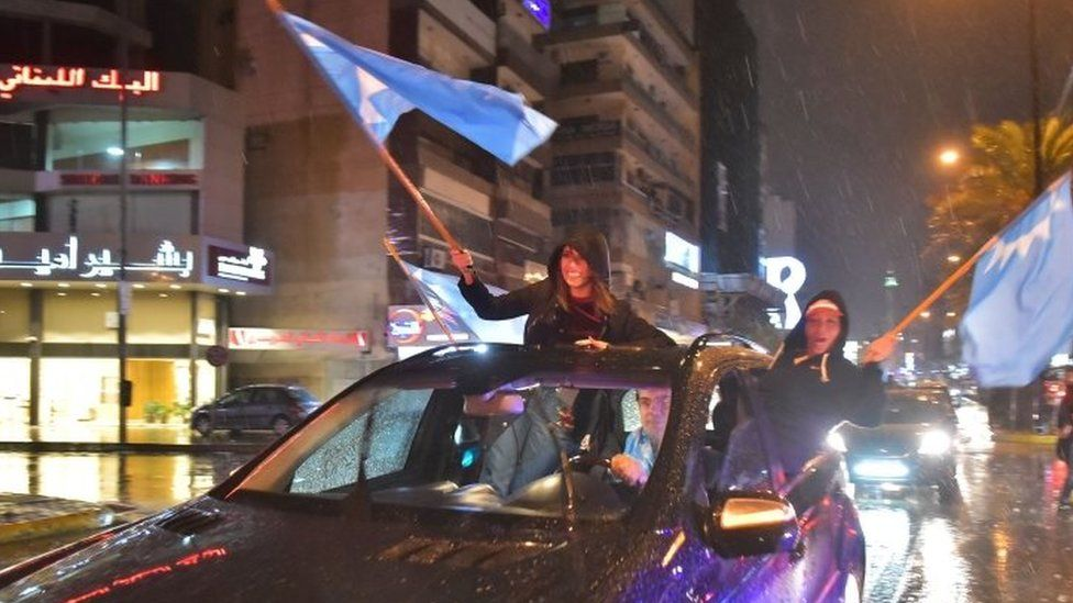 Supporters of Lebanese Prime Minister Saad Hariri wave flags as they celebrate his return to Beirut
