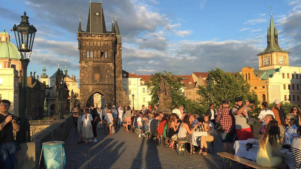 Residents dine at a long table set in Prague