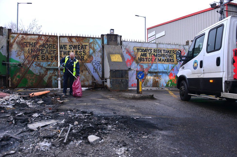 A council worker clears debris from a road on which rioting took place in west Belfast