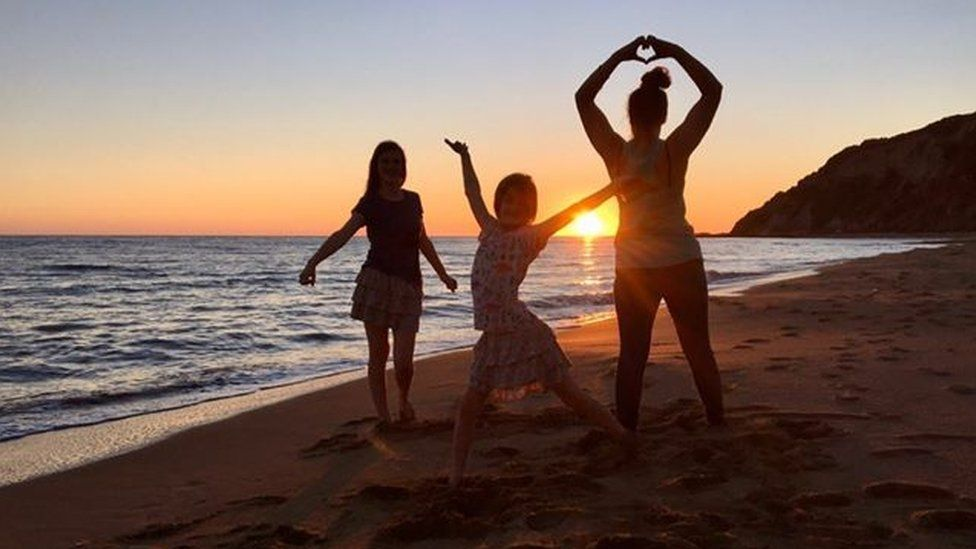 Katie, Shannon and Phoebe Thacker in front of a sunset on the beach