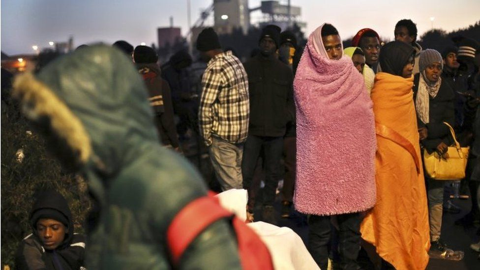 """Migrants wait to register outside a processing centre in the makeshift migrant camp known as """"the jungle"""" near Calais, northern France, on 27 October"""