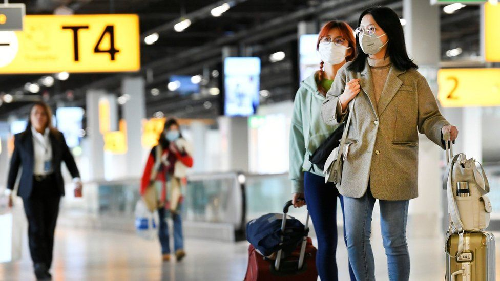 Three travellers at Amsterdam's Schiphol Airport wearing masks