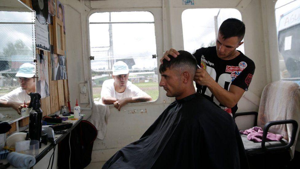 An inmate at work at the barber shop