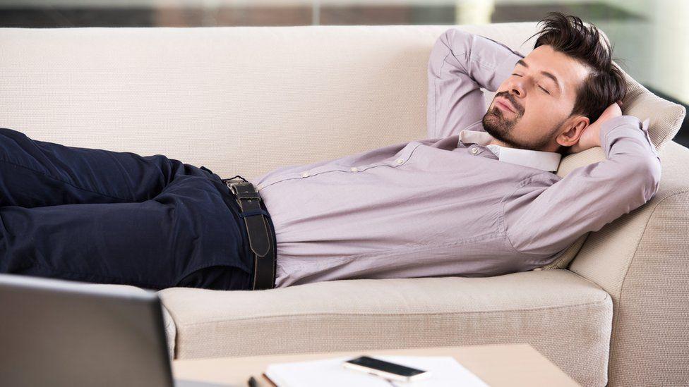 Businessman asleep on sofa