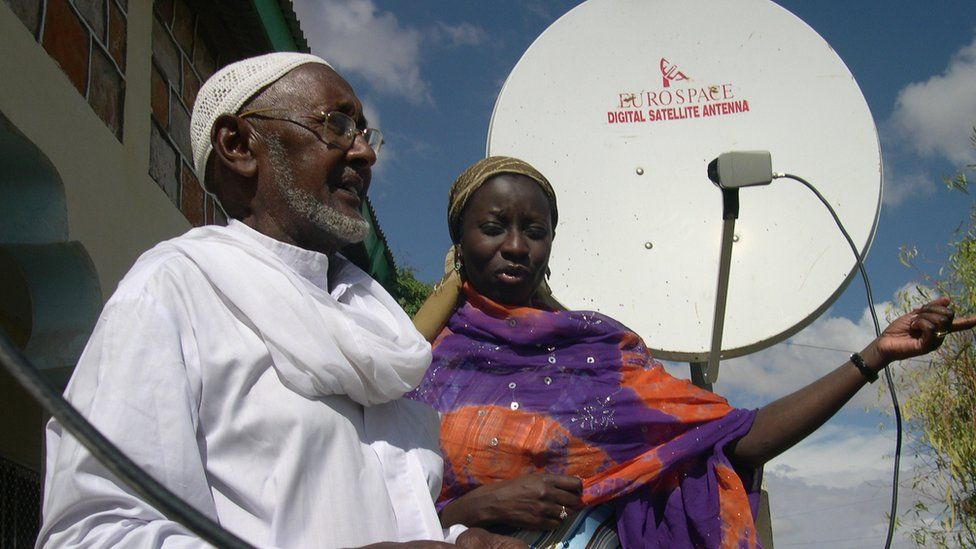 A man and a woman in Somaliland stand in front of a satellite dish.