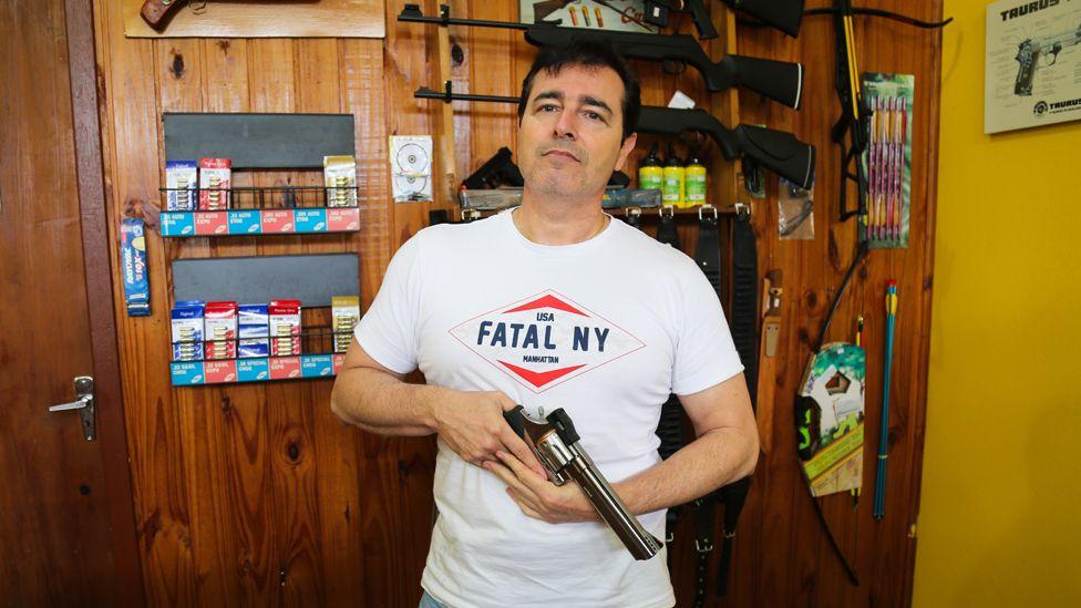 Henrique Nogueira poses with a gun