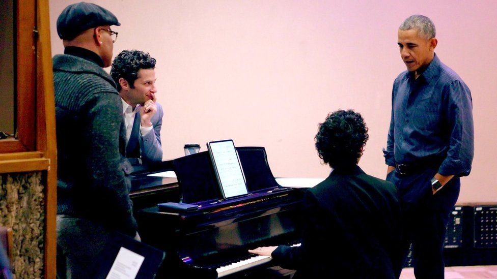 Four men stand around a piano. One of them is former US President Barack Obama