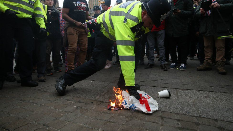 A police officer extinguishes a flag that was set alight by pro-Brexit protestors outside the Houses of Parliament