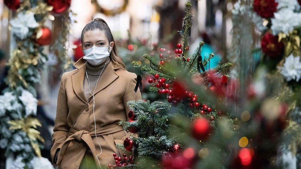 Woman in face mask by Christmas decorations