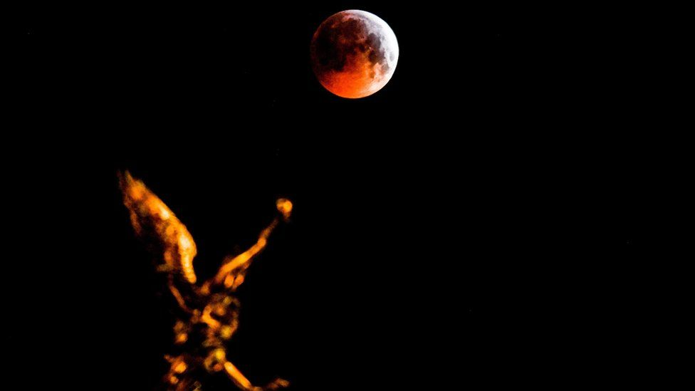 The so-called Super Blood Wolf Moon is seen over a Pheme sculpture on a rooftop of the Academy of Fine Arts in central Dresden, Germany