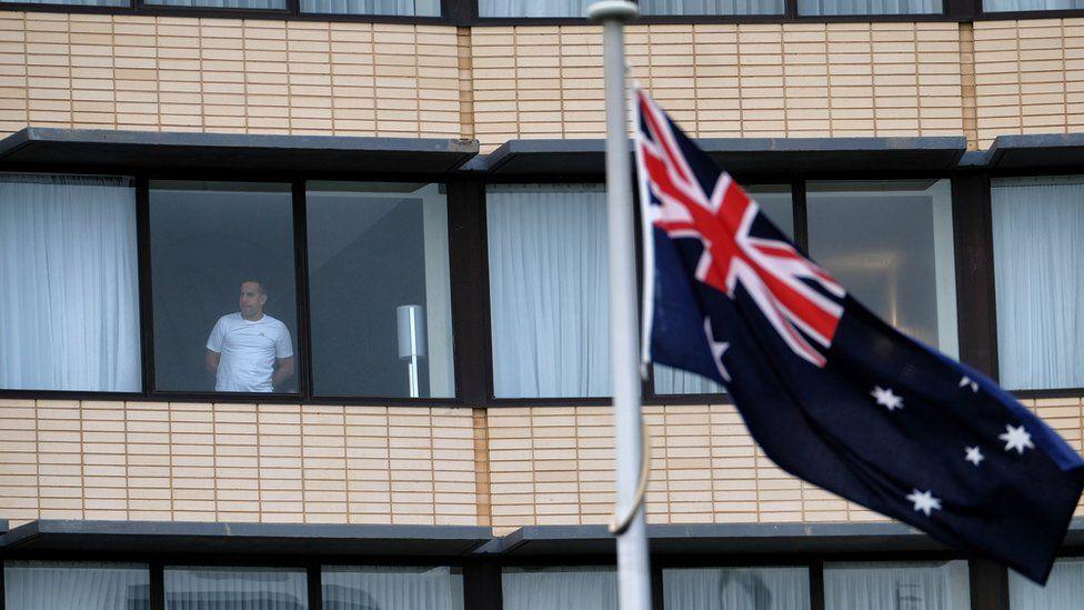 ธงชาติออสเตรเลียบินอยู่หน้าอาคารโรงแรมที่ชายคนหนึ่งมองออกไปจากห้องกักกันของเขา