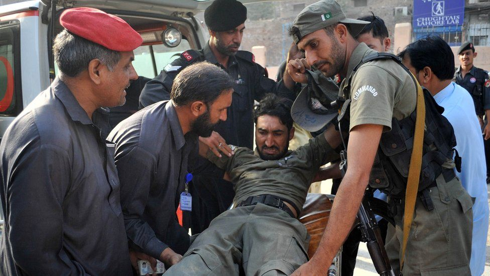 Pakistani security personnel help an injured comrade following an attack on a Pakistan Air Force base in Peshawar - 18 September 2015