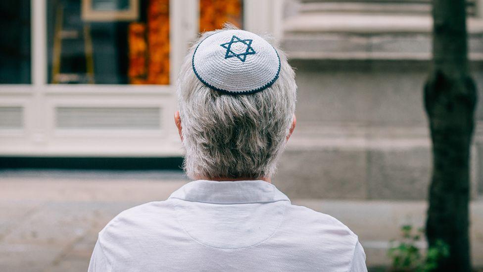 A Jewish man wearing a kippah sits on a bench in London