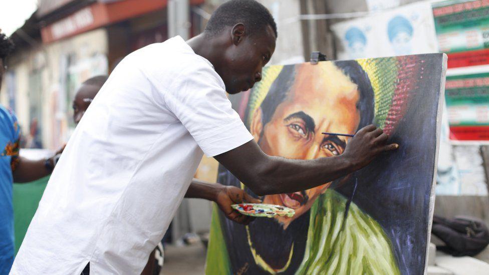 Ghanaian Artist Ibrahim Botchwey at work Chale wote street art festival in Accra-Ghana