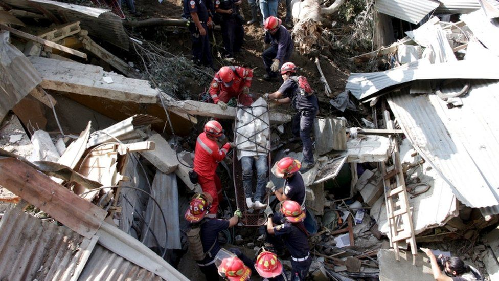 Rescue team members retrieve the body of a landslide victim in Santa Catarina Pinula, on the outskirts of Guatemala City, October 2, 2015.
