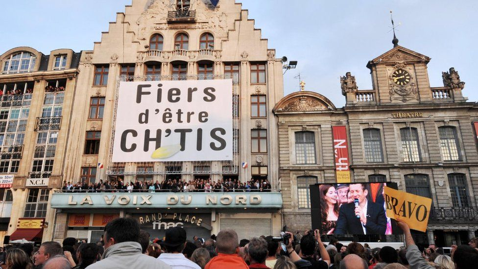 Town hall in northern France with crowd and large banner reading 'Proud to be from the Sticks'