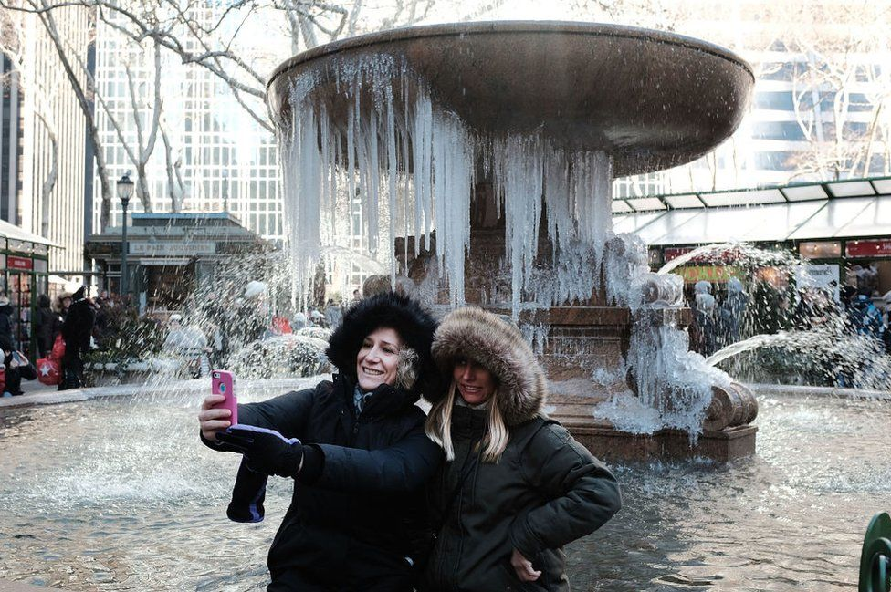 New York tourists take selfie in front of frozen fountain