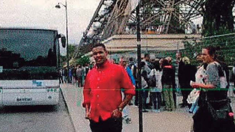 Omar Hychami standing beside the Eiffel Tower in Paris