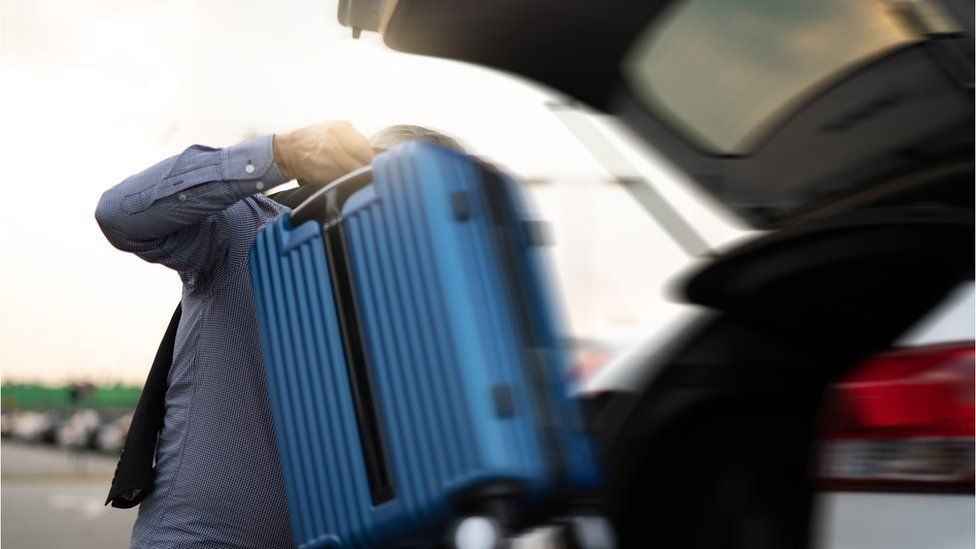 man removing suitcase from back of car