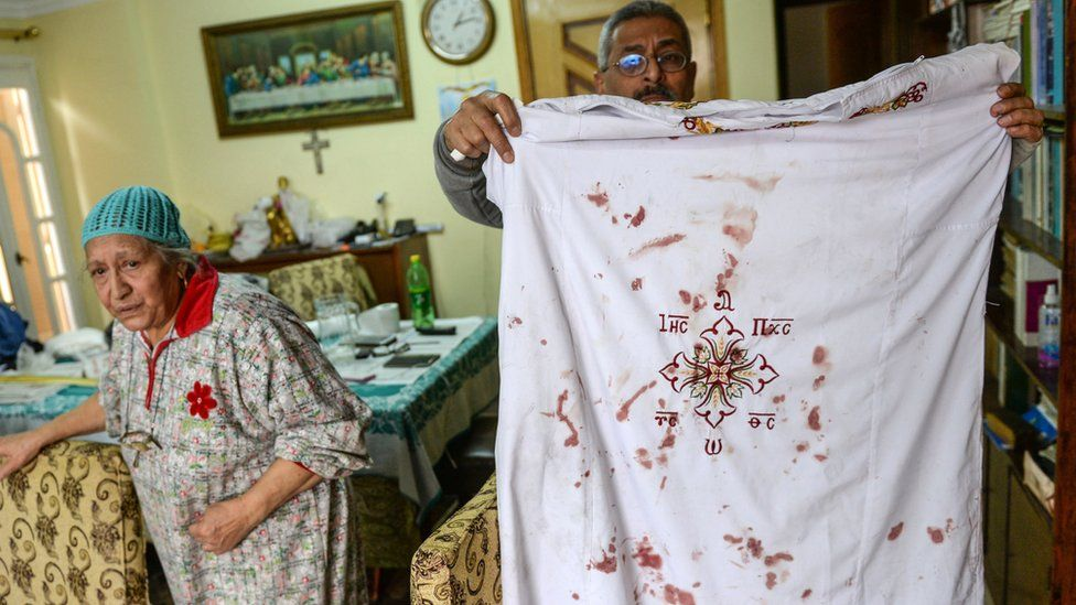 A man holds a Coptic clergy clothes with blood stains on them at Mar Girgis church after a bomb explosion