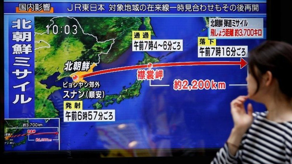A passer-by looks at a TV screen reporting news about North Korea's missile launch in Tokyo (15 September 2017)