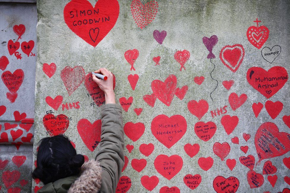 A person paints on the National Covid Memorial wall beside St Thomas' hospital set as a memorial to all those who have died so far in the UK from the coronavirus disease (COVID-19), amid the coronavirus pandemic in London