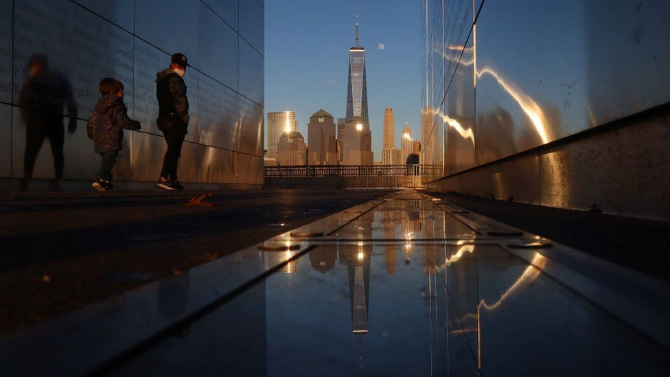 People walk through the Empty Sky 9/11 Memorial as the moon rises next to One World Trade Center in New York City at sunset on February 25, 2021 as seen from Jersey City, New Jersey