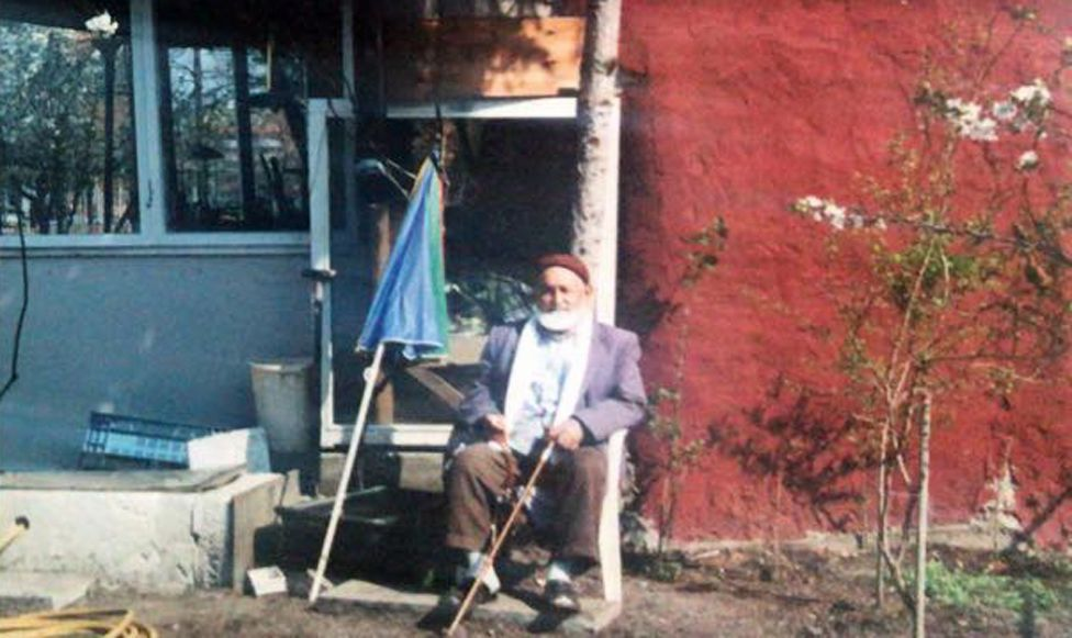 Osman in front of his house