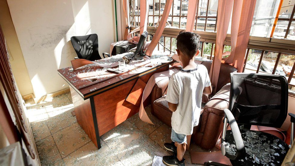 A boy stands amid broken glass inside a Hezbollah media office in southern Beirut, Lebanon (25 August 2019)